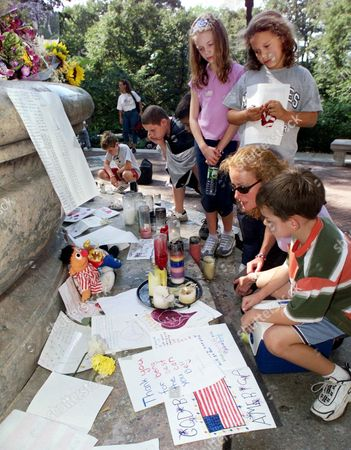 """GRAFF Ilene Graff, of New City, N.Y., kneeling second from right, reads aloud letters of support placed at the firefighter's memorial in New York's Upper Westside, Wednesday afternoon, . The monument is dedicated """"to the heroic dead of the fire department"""