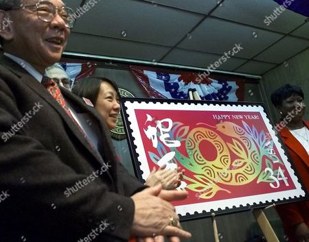 LEE MATSUDA MALLOY Sam Lee, left, representing the Chinese Benevolent Association, Fay Chew Matsuda, Director of the Museum of Chinese in the Americas, center, and New York District Postmaster Vinnie Malloy, right, celebrate the unveiling of the U.S. Postal Service's Year of the Snake stamp, in New York's Chinatown. This year's stamp is the ninth in a series of 12 commemorating the Chinese lunar New Year by the U.S. Postal Service