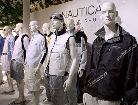 A group of mannequins line the stage wearing examples of the Nautica Spring 2002 collection by David Chu, as show assistants prepare the set, background, in New York
