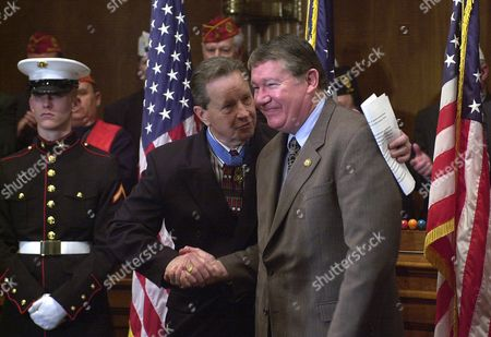 "BRADY CUNNINGHAM Retired Maj. Gen. Patrick Brady, center left, a Medal of Honor winner, shakes hands with Rep. Randy ""Duke"" Cunningham, R-Calif., after Cunningham spoke in support of the ""Flag Protection Constitutional Amendment,"" which would make desecrating the American flag illegal, on Capitol Hill, in Washington. Cunningham, a former U.S. Navy fighter pilot, was shot down during the Vietnam War"