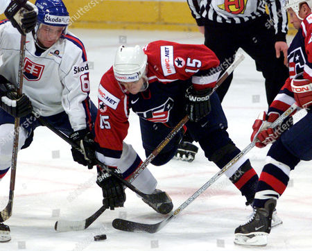 Slovakia's Peter Pucher, left, fights for the puck with US Jeff Halpern, center, of Washington Capitals and Doug Brown of the Detroid Red Wings, during the Icehockey World Championship final round group F match Slovakia versus USA at the KoelnArena in Cologne, western Germany