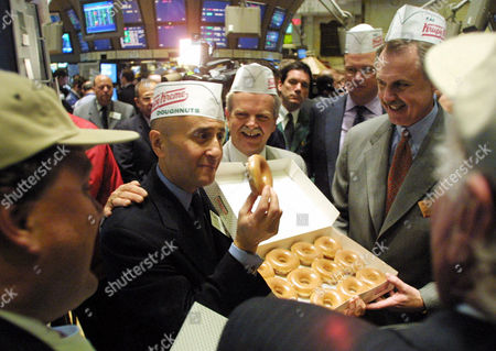 GRASSO TATE LIVENGOOD FILE **Richard Grasso, second from left, then chairman of the NYSE, holds a doughnut on the floor of the exchange with John Tate, center, COO of Krispy Kreme Doughnuts Inc., and Scott Livengood, second right, CEO of Krispy Kreme Doughnuts Inc., May 17, 2001. Tate has submitted his resignation, effective mid-September, the company said . Livengood will assume Tate's responsibilities, said Amy Hughes, the company spokeswoman