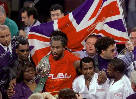 Stock Picture of LEWIS TUA Lennox Lewis of London, England, center, with the WBC belt on his right shoulder celebrates with his mother Violet Lewis, left, and trainer Emmanuel Steward, second right, after retaining his titles against David Tua of Auckland, New Zeland, in the Heavyweight Championship bout, at the Mandalay Bay Resort & Casino in Las Vegas