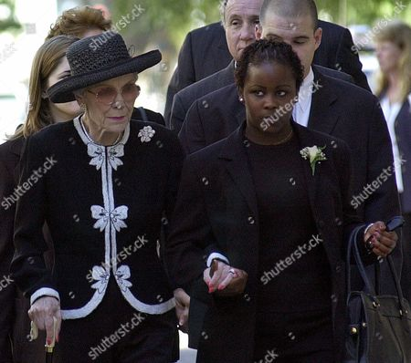 REVELL WYMAN MIREMBE CROP--Jane Wyman, mother of Maureen Reagan, left, holds hands with Rita Mirembe Revell, the adopted daughter of Maureen Reagan, as they arrive for memorial services for Reagan, at the Cathedral of the Blessed Sacrament in Sacramento Calif