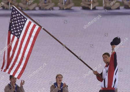 KRAYZELBURG U.S. Olympic swimming medalist Lenny Krayzelburg holds the U.S. flag, saluting as he leads the U.S. delegation entering Jerusalem's Teddy Stadium during the opening ceremony of the 16th Maccabiah Games . Thousands of Jewish athletes from around the world will participate in the competitions which were reduced from 11 days to 8 due to security fears in the midst of ten months of fighting with the Palestinians that almost forced the cancellation of the games