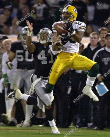 FERGUSON JOHNSON Green Bay Packers wide receiver Robert Ferguson catches a pass for a first down despite the efforts of Oakland Raiders safety Eric Johnson during the third quarter in Oakland, Calif