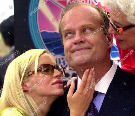 "GRAMMER Actor Kelsey Grammer, who plays Dr. Frasier Crane on the NBC comedy ""Frasier,"" and formerly an actor on the sitcom ""Cheers,"" smiles as his mother Sally, right, and his wife, Camille, get ready to kiss him after he was honored with a star, on the Hollywood Walk of Fame in Los Angeles. The location of the star is in front of the Hollywood Entertainment Museum where the original ""Cheers"" bar set is displayed"