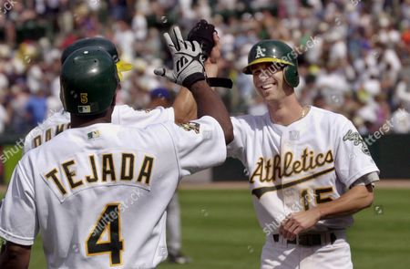 HUDSON DAMON TEJADA Oakland Athletics pinch runner Tim Hudson, right, is congratulated by teammates Johnny Damon, partially obscured, and Miguel Tejada (4) after Hudson scored the winning run on a single by Eric Chavez in the 10th inning against the Texas Rangers, in Oakland, Calif. The Athletics won 5-4