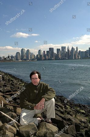 """BURNS Filmmaker Ric Burns poses at Liberty State Park in New Jersey on . The New York skyline behind him lacks the once-prominent World Trade Center towers, destroyed in the Sept. 11 terrorist attack. They are among the architectural features of New York in the last chapter of Burn's """"New York: A Documentary Film,"""" whose final 4 1/2 hours air on PBS stations Sunday and Monday, Sept. 30 and Oct. 1, 2001"""