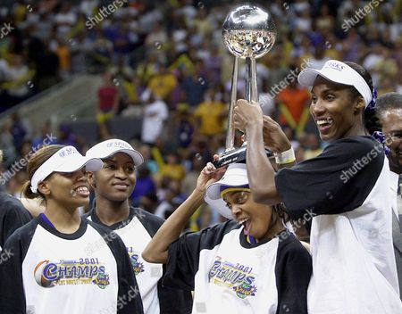 MABIKA Los Angeles Sparks' Lisa Leslie, right, holds the WNBA championship trophy on the head of teammate Nicky McCrimmon as Tamecka Dixon, left, and Mwadi Mabika, second left, look on as they celebrate their first WNBA title by defeating the Charlotte Sting, 82-54, in Los Angeles