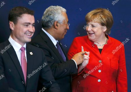 German Chancellor Angela Merkel, right, gestures as she talks to Portuguese Prime Minister Antonio Luis Santos da Costa next to Estonian Prime Minister Taavi Roivas, left, during an EU summit group photo in Brussels, Belgium, . British Prime Minister Theresa May is set to hold her first talks with EU leaders and will tell them that the U.K.'s decision to leave the bloc is irreversible
