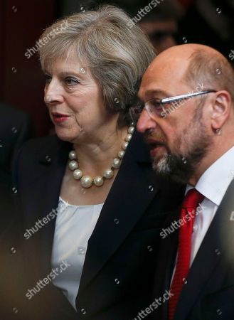 European Parliament President Martin Schultz, right, talks to British Prime Minister Theresa May as they arrive for the EU summit group photo in Brussels, Belgium, . British Prime Minister Theresa May is set to hold her first talks with EU leaders and will tell them that the U.K.'s decision to leave the bloc is irreversible