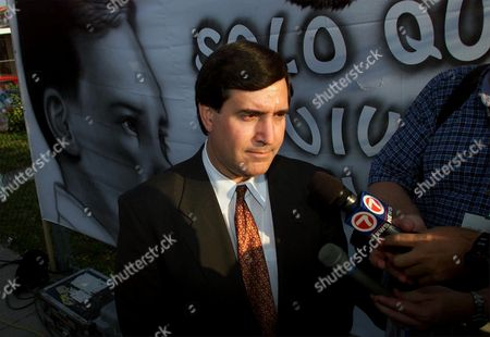 CAROLLO Miami Mayor Joe Carollo stands next the image of six-year-old Elian Gonzalez, as he waits to be interviewed across the street from the home of Elian's relatives in Miami, Fla