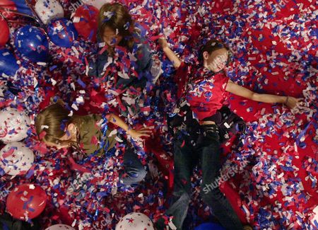 Claire, left, Emily, center, and Sarah Morgan, from Baton Rouge, La., play in the confetti on the foor of Madison Square Garden at the end of the Republican National Convention in New York