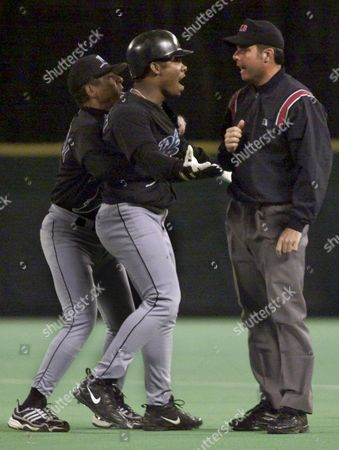 GUILLEN Tampa Bay Devil Rays' Jose Guillen, center, is restrained by coach Jose Cardenal, left, as Guillen argues with first base umpire Tim Timmons after he was called out at first in the fourth inning against the Philadelphia Phillies