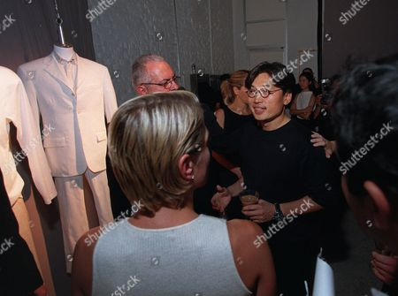 CHU Fashion designer David Chu is the center of attention at his showing of the Nautica Men's Spring 2000 Collection in New York . A white cotton polyurethane coated suit with ice gray cotton short sleeve shirt is displayed in the background during this modeless show