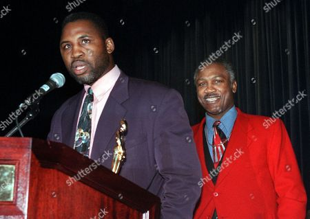 "FRAZIER Boxer Smokin' Joe Frazier, right, listens as his son, Marvis, speaks after receiving a ""Father of the Year Award"", in New York. Six men were honored, including basketball hall of famer Walt Frazier, TV personality Bill Boggs, actor Gerald McRaney, Admiral Jay L. Johnson and business leader Paul R. Charron, at the 65th annual luncheon"