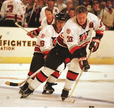 ROBBINS MORANIS Actor-director Tim Robbins, right, is followed by teammate Rick Moranis, left-helmet, during action, at the celebrity hockey match at the Worcester Centrum in Worcester, Mass., between the Hollywood All-Stars and Boston Bruins alumni. The game was for the benefit of the Denis Leary Firefighters Association
