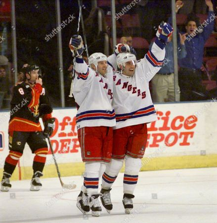 TAYLOR DAIGLE BURE New York Rangers' Tim Taylor, left, and Alexandre Daigle celebrate Taylor's game-winning goal in overtime against the Calgary Flames, at Madison Square Garden in New York. Daigle got an assist in the 3-2 win. Flames Valeri Bure is at rear left