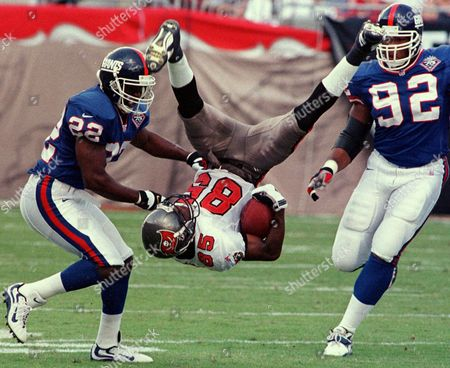 ANTHONY SPARKS STRAHAN Tampa Bay Buccaneers wide receiver Reidel Anthony (85) gets flipped over by New York Giants defenders Phillippi Sparks (22) and Michael Strahan (92) after making a first quarter reception Sunday afternoon at Raymond James Stadium in Tampa, Fla