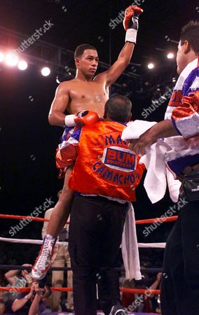 HECTOR CAMACHO JR Hector Camacho Jr. of Orlando, Fla., is raised by his trainer after defeating Philip Holiday of South Africa during the sixth round of their super lightweight championship bout, in Phoenix