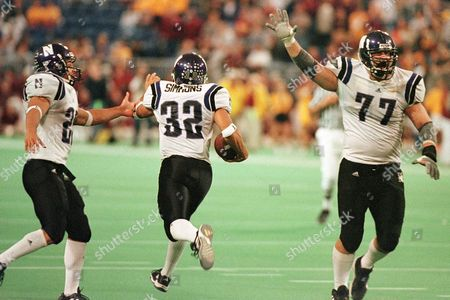 Stock Image of SIMMONS ADAMS CLELLAND Northwestern's Sam Simmons (32) is congratulated by teammate Jarvis Adams, left, while Lance Clelland (77) begins to celebrate as Simmons runs out of the end zone after making the game-winning catch on the final play of the game with Minnesota 41-35, in Minneapolis