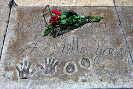 "YOUNG A bouquet of roses lies near the hand and shoe prints of Loretta Young at the Mann's Chinese Theater, in the Hollywood section of Los Angeles. Young, the elegant beauty whose acting career extended from silent movies to television and included an Academy Award for best actress in ""The Farmer's Daughter,"" died Saturday of ovarian cancer, according to Norman Brokaw, her longtime agent and friend. She was 87"