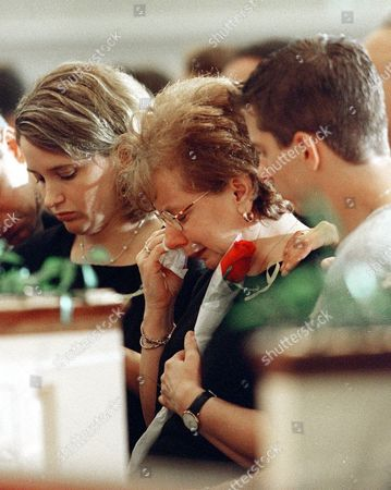 REMEMBRANCE Marie Quinn, center, wife of Edward Quinn one of the Atlanta shooting victims, is comforted by family during a Service of Hope and Remembrance at the Peachtree Road United Methodist Church in Atlanta