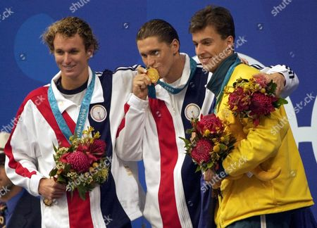 KRAYZELBURG WELSH PEIRSOL U.S. swimmer Lenny Krayzelburg, center, kisses his gold medal for the men's 200m backstroke as he stands with his teammate and silver medal winner Aaron Peirsol, left, and Australian bronze medal winner Matthew Welsh, right at the Sydney International Aquatic Center during the Summer Olympics in Sydney