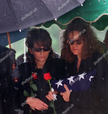 Stock Photo of PUENTE Protected from the rain by umbrellas, Audrey Puente, left, and Margie Puente, the daughter and wife respectively of musician Tito Puente, say final farewells at his gravesite, in Nanuet, N.Y. Puente died Thursday, June 1, at age 77