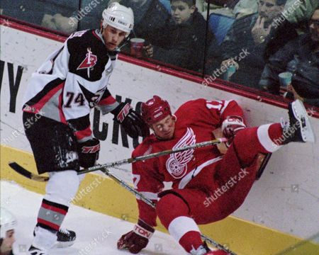 MCKEE Buffalo Sabres defenseman Jay McKee (74) checks Detroit Red Wings right winger Doug Brown (17) off his skates and into the boards during the first period at the Marine Midland Arena in Buffalo, N.Y. on