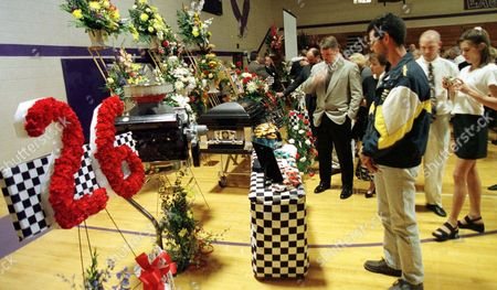 Mourners look at photos and racing memorabilia after the funeral of race car driver Tony Roper in Fair Grove, Mo., . Roper, 35, died Saturday of injuries suffered Friday night when he crashed into a wall at the Texas Motor Speedway in Fort Worth, Texas, Friday
