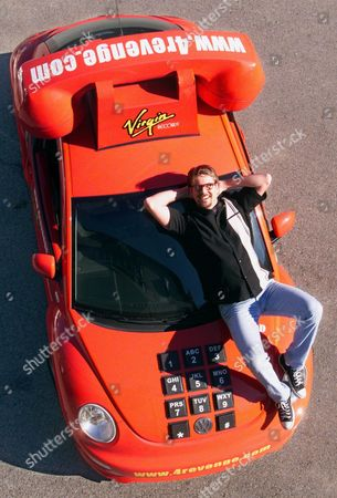 """MABE Comedian Tom Mabe shows off the VW Bug remodeled to look like a giant telephone he used to promote his CD on Virgin Records titled """"Revenge on the Telemarketers, Round One,"""" during a visit to Nashville, Tenn., in this Jan. 6, 2000 photo. Mabe went undercover at a telemarketing convention in the nation's capitol, to turn the tables on an industry he loves to hate. He was on the phone calling telemarketers in their hotel rooms before dawn Monday"""