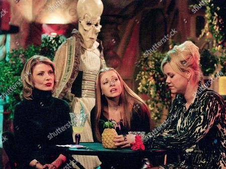 "HART BRODERICK RHEA Melissa Joan Hart, star of the WB network series ""Sabrina, the Teenage Witch,"" sits with series co-stars Beth Broderick, left, and Caroline Rhea, who play fellow witches Zelda and Hilda, respectively, as an alien figure passes behind them during a break from shooting on the series set at Paramount Studios, in Los Angeles. The sitcom will mark its 100th episode on Friday, Oct. 27"