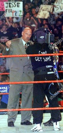 """VENTURA LAWLER Minnesota Governor Jesse Ventura reacts as he is interviewed by commentator Jerry Lawler, behind cameraman, before the World Wrestling Federation's """"Raw is War"""" event at the Allstate Arena, in Rosemont, Ill. The former wrestling star flew from St. Louis, the site of the governors' gathering, to promote his appearance later this month as a guest referee at a WWF title match"""