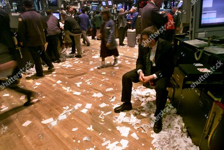 Stock Photo of SENNOTT Specialist Tad Sennott, seated right, takes a breather after the closing bell on the floor of the New York Stock Exchange, . The Dow Jones industrial average closed down 616.23 points to 10,307.32. It was the largest one day point drop ever for the Dow Jones industrial average