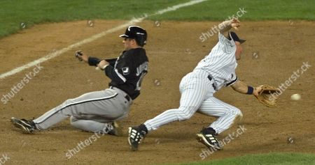 JOHNSON BROSIUS Chicago White Sox' Mark Johnson slides safely into third base on a RBI hit to right field by Greg Norton in the fifth inning, at Yankee Stadium in New York. Yankees third baseman Scott Brosius makes lunging attempt but can't get to an errant throw from Paul O'Neill