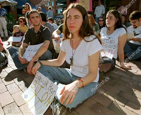 NICE ABELING KELLY Aaron Nice, left, Lisa Abeling, center, and Kristen Kelly join others during a sit-down protest on a street corner in downtown Tempe, Ariz., . Some 40 demonstrators gathered for a peaceful protest against the city's recently adopted law banning sitting and lying on city sidewalks. The new law arose following complaints from Tempe business owners about loitering outside their shops