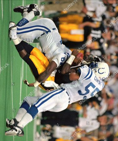 Stock Photo of STEWART JOHNSON CORYATT Pittsburgh Steelers quarterback Kordell Stewart, center, is sandwiched on a run by Indianapolis Colts linebacker QuentIn Coryatt (55) and defensive lineman Ellis Johnson (62) in the first half of the game in Pittsburgh on . Stewart received a concussion on the play and did not start the second half