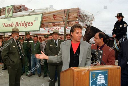 """MARIN Actor Don Johnson gestures toward a load of 23 tons of lumber he purchased to aid in the preservation of the ferryboat Eureka at Aquatic Park in San Francisco, . At Johnson's left is actor Cheech Marin. Looking on are workers with the National Park Service and U.S. Park Police. The Eureka, a National Historic Landmark, serves as Johnson's police headquarters on the television show, """"Nash Bridges."""" The Eureka carried railraod freight cars and passengers on San Francisco Bay until1957"""
