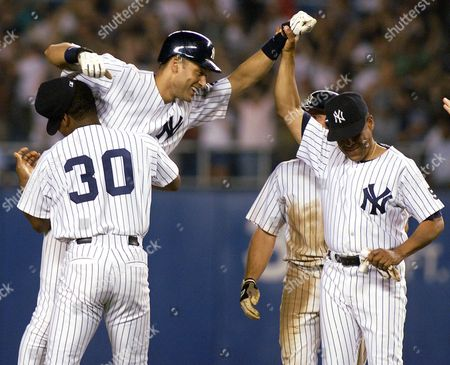 JETER RANDOLPH CARDENAL New York Yankees Derek Jeter is hoisted by third base coach Willie Randolph (30) and first base coach Jose Cardenal after Jeter's two-rbi, game-winning hit in the tenth inning against Cleveland Indians at Yankee Stadium in New York, . The Yankees won 9-8