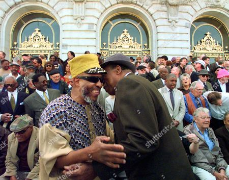 "Stock Image of Handy Hand Saxophonist John Handy, left, greets Ameal Hand, a bassist, in front of 150 jazz musicians from the Bay Area at San Francisco's City Hall on . The musicians were invited for a historical photo that mimics the ""Great Day in Harlem"" photo in New York in the 1950's, that was the subject of a documentary film"