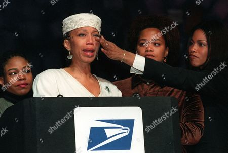 SHABAZZ Ilyasah Shabazz, right, wipes a tear from the cheek of her sister, Attallah Shabazz, as her other sisters, Qubilah, left, and Malaak Shabazz watch from behind the podium during the dedication ceremony of the stamp honoring their late father, slain civil rights leader Malcolm X, in New York