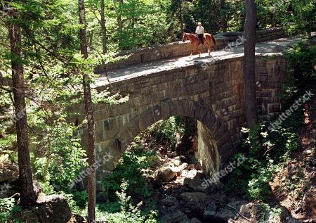 """CARRIAGE ROADS A horse and rider crosses the Waterfall Bridge on the Sargent Mountain carriage road at Acadia National Park on Mt. Desert Island, near Bar Harbor, Maine. John D. Rockefeller, Jr. planned 16 distinctive stone-faced bridges to be harmonious with the park's surroundings. David Rockefeller, his son, turns 100 on June 12, 2015, and will celebrate by transferring his family property at Little Long Pond in Seal Harbor to the Mount Desert Island & Garden Preserve, describing it as a """"gift to all the people of Maine"""