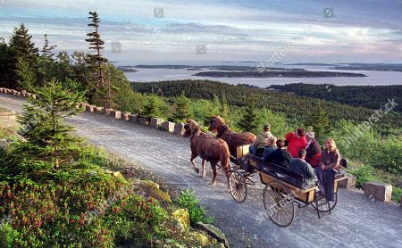 A carriage ride brings visitors to the summit of Day Mountain at Maine's Acadia National Park, overlooking the Cranberry Islands off shore. While designing carriage roads in the park, John D. Rockefeller, Jr., gave top importance to the scenic views. David Rockefeller, his son, turns 100 on June 12, 2015, and will celebrate with a gift to the people of Maine: 1,000 acres of woodlands, streams, hiking trails and carriage roads abutting Acadia National Park