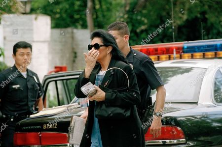 An unidentified woman is accompanied by a police officer after arriving at the home of actor and comedian Phil Hartman in the Encino section of Los Angeles, Calf., . Hartman, an alumnus of Saturday Night Live and actor on NBC's News Radio, and his wife were found dead in their home in the morning. Police officers responding to a 911 call were removing two children from the home when Hartman's wife, Brynn, 40, killed herself in another part of the house, Lt. Anthony Alba said