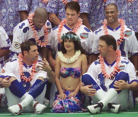 RO NFC Pro Bowl quarterbacks Steve Young (8) and Chris Chandler (12) carry on a conversation around a Hawaiian hula dancer as they wait for the team photo to be taken in Honolulu, Hawaii. Behind the quarterbacks are Green Bay's LeRoy Butler (36), Tampa Bay's Mike Alstott, and Atlanta's Eugene Robinson