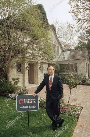 Realtor Fred Sands stands next to his company?s sign in front of O.J. Simpson?s former estate in the Brentwood section of Los Angeles, . The home, which is listed at $3.95 million, was vacated by Simpson after a jury found him liable for $33.5 million for the killings of his former wife Nicole Brown Simpson and Ron Goldman