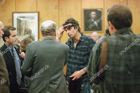 Stock Photo of Tommy Lee Sporting braided locks, rock musician Tommy Lee talks with his legal team in court, in Malibu, California in a probation hearing to determine if he violated terms of his probation for allegedly consuming alcohol. From left are spokesman Allan Mayer, attorney Steve Gold, and counselor Gerald Rafferty. Lee, estranged husband of Pamela Anderson Lee, was on probation for a charge of assault on a photographer and had been jailed for several months after an alleged assault on his wife. Lee remained free after Thursday?s hearing was continued to March 10 by Judge Lawrence Mira, far right rear, after his probation officer failed to appear in court
