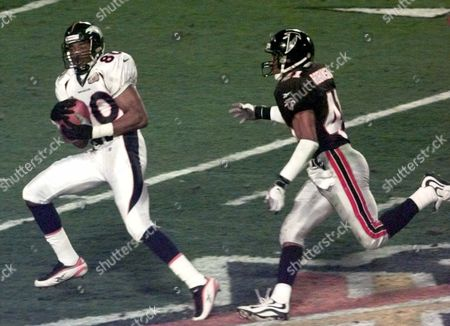 Stock Image of SMITH ROBINSON Denver Broncos wide receiver Rod Smith (80) catches an 80-yard touchdown pass from quarterback John Elway as Atlanta Falcons safety Eugene Robinson (41) defends in the second quarter of Super Bowl XXXIII, in Miami